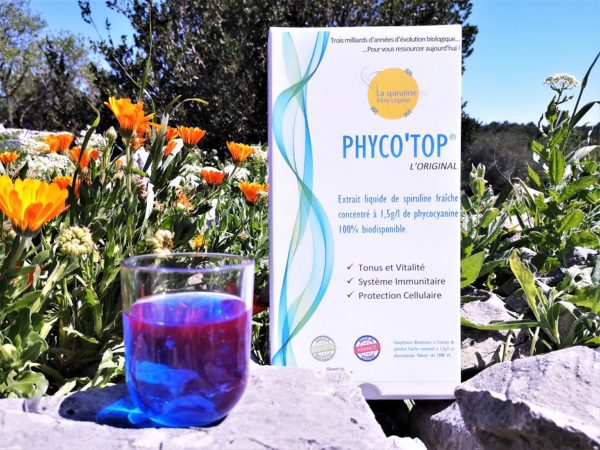Boite Phyco'Top et verre de Phycocyanine au soleil